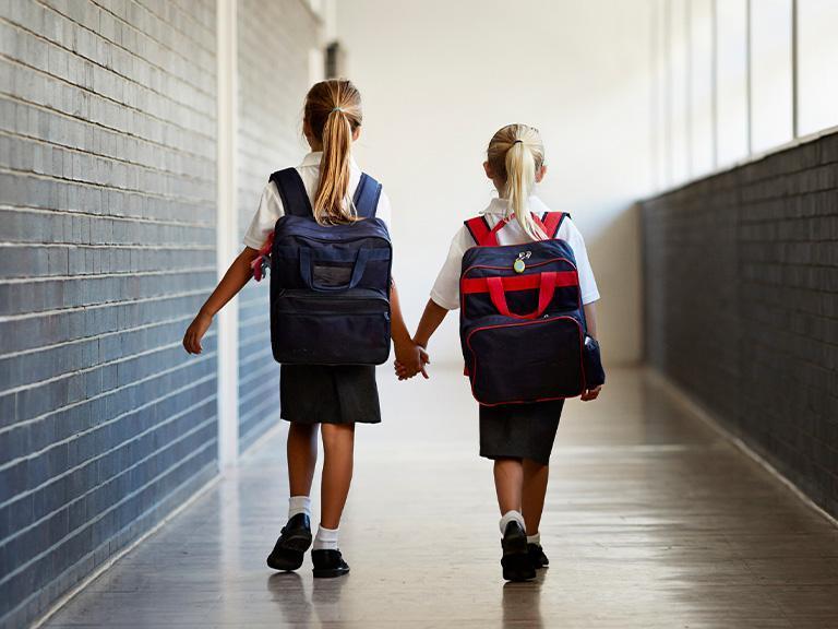 dwie dziewczynki idące trzymającsię zaręce